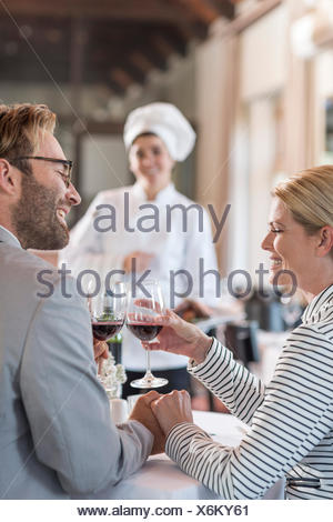 Mid adult couple in restaurant toasting with redwine - Stock Photo