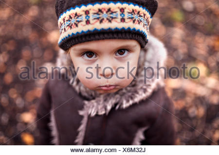 Portrait of pouting little girl in autumn - Stock Photo