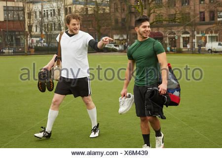 Two male soccer players carrying gym bags on soccer pitch - Stock Photo