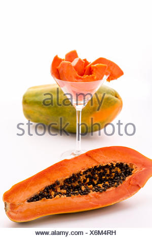 A papaya fruit in longitudinal section, its fruit pulp assorted in a cocktail glass and a whole fruit. - Stock Photo
