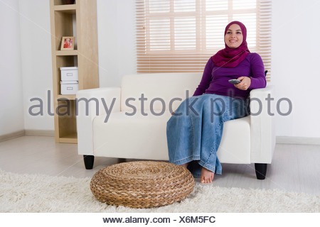 Woman holding the television remote control - Stock Photo