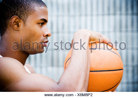 Portrait of a young African American man holding a basketball. - Stock Photo