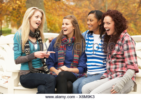 Group Of Four Teenage Girls Sitting On Bench In Autumn Park - Stock Photo