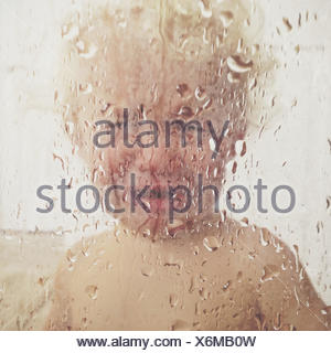 Boy standing in the shower crying - Stock Photo