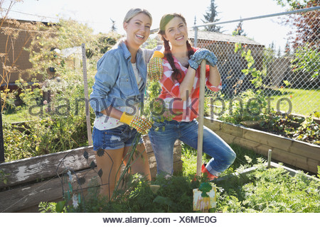Portrait of female friends standing together in garden - Stock Photo