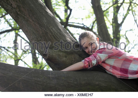 Portrait of young girl lying on top of tree branch - Stock Photo