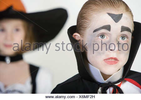 Boy (7-9), wearing dracula costume, girl in background - Stock Photo