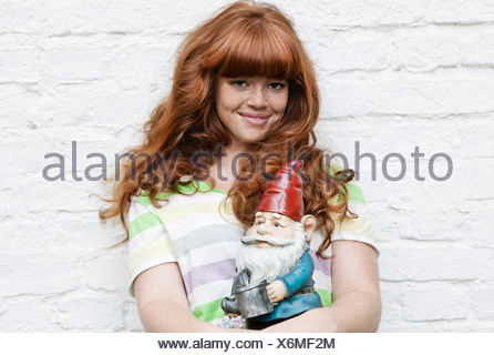 Germany, Berlin, Close up of young woman holding garden gnome, smiling, portrait - Stock Photo