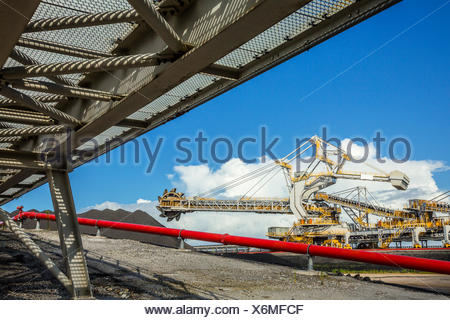 An automated bucket-wheel excavator loads coal into ships bound for China and India. - Stock Photo