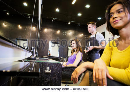Customer with hairstylists in hair salon - Stock Photo