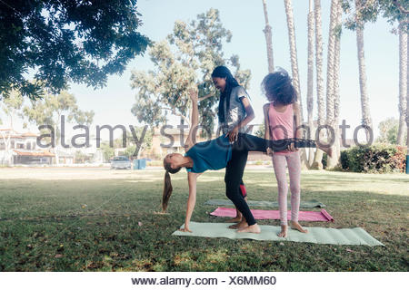 Girls and teenage schoolgirls practicing yoga standing half moon pose on school playing field - Stock Photo