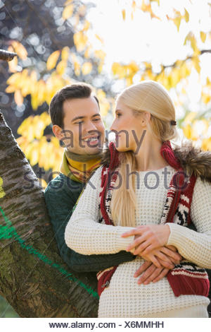 Happy young man hugging woman while leaning on tree trunk during autumn in park - Stock Photo