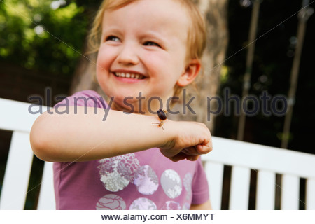 Girl holding snail on arm - Stock Photo