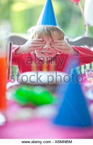 Young boy with hands over eyes at birthday party - Stock Photo