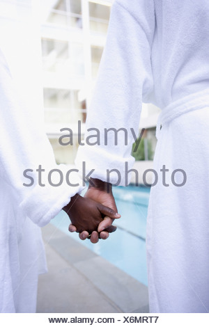 Couple in bathrobes holding hands - Stock Photo