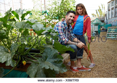 Portrait smiling father and daughter in garden - Stock Photo