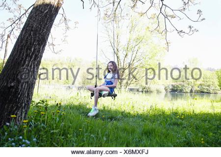 Girl on swing in tree, portrait