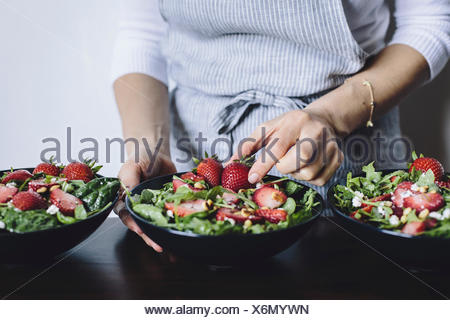 A woman is photographed from the front view while placing a strawberry into a bowl of strawberry spinach and arugula salad. - Stock Photo