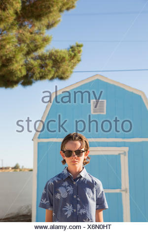 USA, California, Boy (14-15) wearing sunglasses standing in front of blue barn - Stock Photo