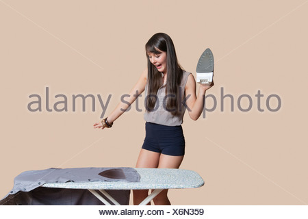 Shocked young woman looking at burnt shirt on ironing board over colored background - Stock Photo