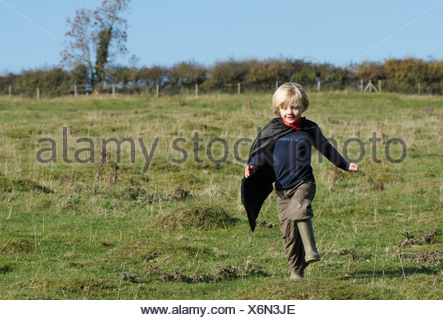 Super Hero boy in countryside - Stock Photo