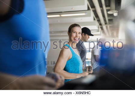 Smiling woman on treadmill at gym - Stock Photo