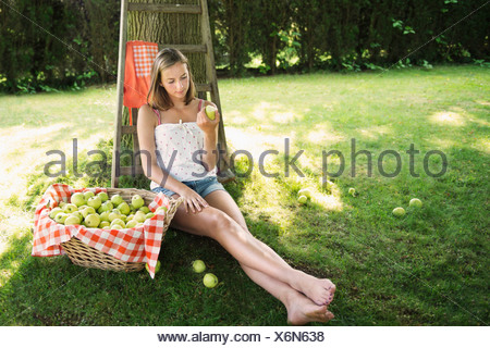 Adolescent girl sitting in orchard eating an apple - Stock Photo