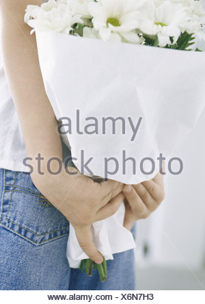 Child holding bouquet of daisies behind back, close-up - Stock Photo