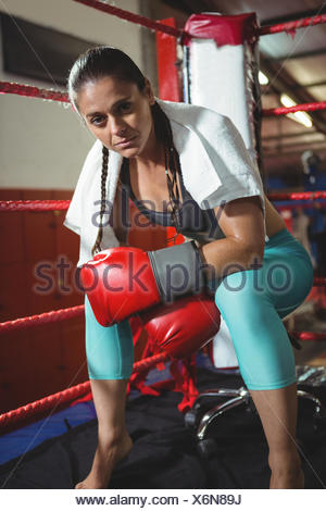 Tired female boxer sitting in the ring - Stock Photo