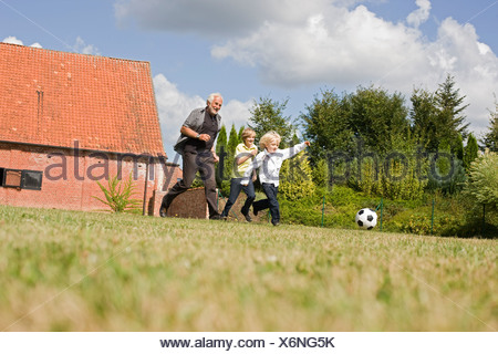 grandfather and kids playing football - Stock Photo