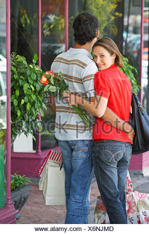 Man and woman outdoors with flowers embracing - Stock Photo
