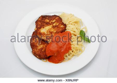 2 Milanese turkey steaks on spaghetti with tomato sugo, basil - Stock Photo