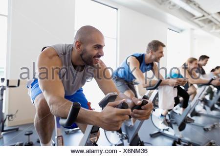 Smiling man enjoying spin class stationary bike gym - Stock Photo