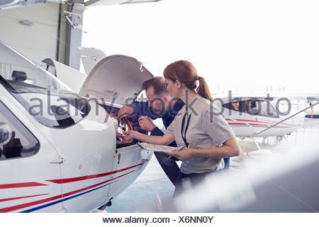Engineer mechanics working on airplane engine in hangar - Stock Photo