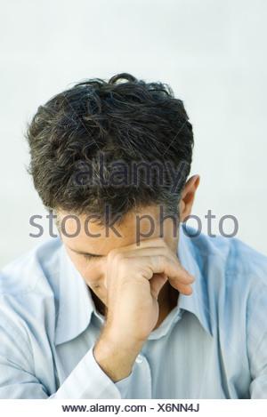 Man leaning head against fist, portrait - Stock Photo