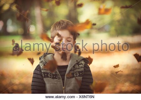 Boy standing in park with autumn leaves falling, Bulgaria - Stock Photo