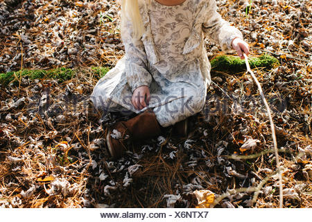 Girl holding stick in forest - Stock Photo