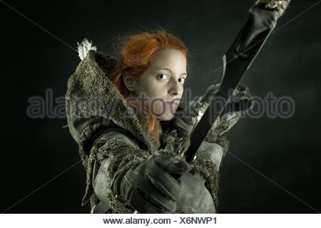 girl archer in a costume with bow isolated in a dark background - Stock Photo