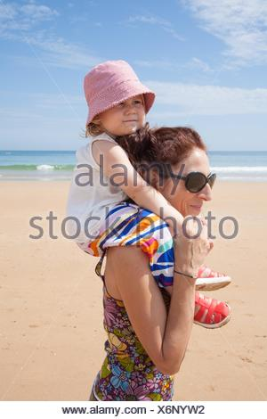 woman mother black sunglasses carrying on shoulders two years old blonde baby with pink hat white shirt and colorful trousers at summer beach. - Stock Photo