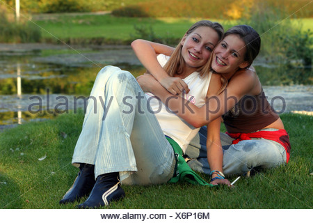 Friendship forever, 2 teenage girls in park smoking a cigarette and embrace and look at camera - Stock Photo