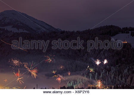 New Year's Eve fireworks in Fieberbrunn, mountains, hotel facility, houses, haze, Tyrol, Austria - Stock Photo