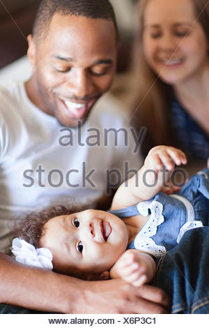 Mother and father playing with baby daughter