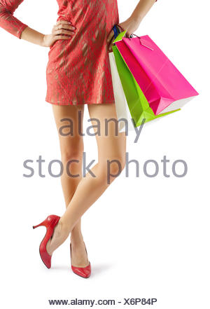 close up view on beautiful female legs and hands with paperbags - Stock Photo