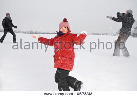 Two parents and their daughters having a snowball fight - Stock Photo