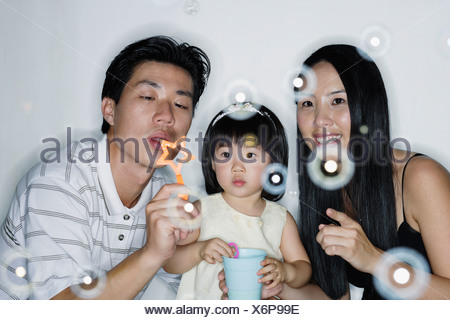 Couple with young girl blowing bubbles - Stock Photo