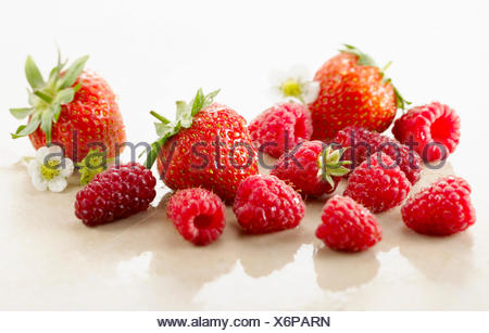 Raspberry, Rubus idaeus cultivar and Strawberry, Fragaria cultivar. Several berries with calyxes and strawberry flowers on white marble. Selective focus. - Stock Photo