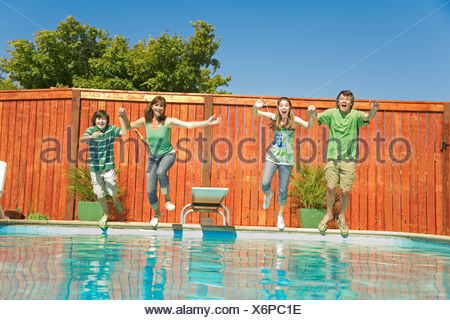 Family jumping into swimming pool - Stock Photo