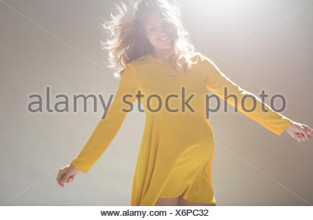 Studio portrait of pregnant young woman twirling around - Stock Photo