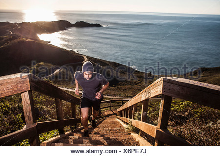 Young man running up coastal staircase at sunset - Stock Photo