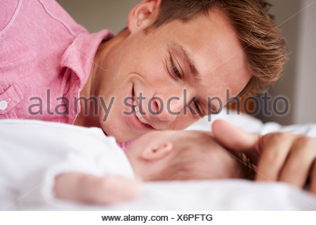 Father Playing With Baby Girl As They Lie In Bed Together - Stock Photo